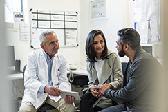 Doctor discussing with couple over digital tablet